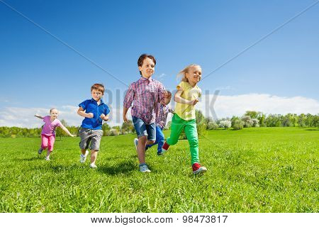 Happy group of children running in the green park