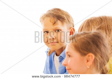 Nice portrait of boy among kids with modest smile