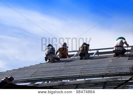 Construction Workers Install A Steel Roof.