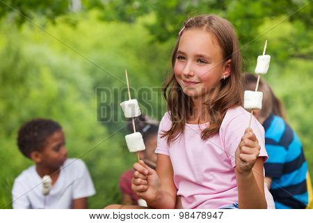 Smiling girl holding marshmallows near tent