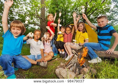 Teens with arms up near bonfire hold marshmallow