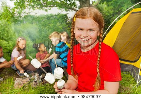 Smiling girl camping and holding  marshmallows