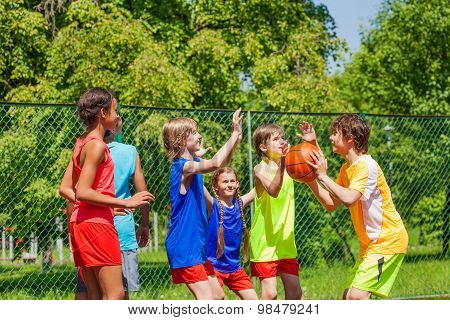 Happy friends playing basketball game outside