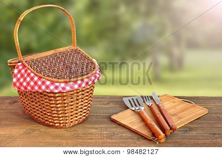 Close-up Of Picnic Banch With Hamper And Bbq Grill Tools