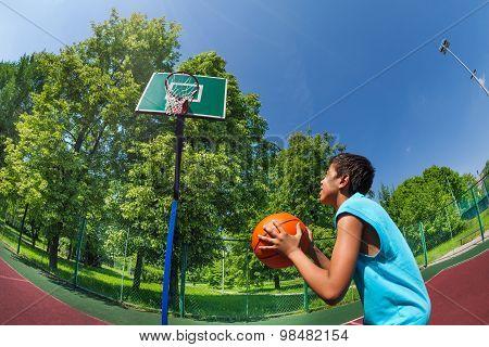 Arabian boy ready to throw ball in basketball goal