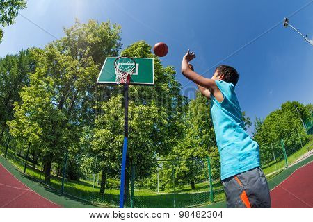 Arabian boy throws ball in basketball goal