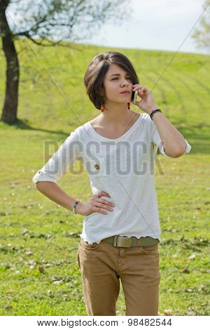 Beautiful young woman looks annoyed while talking on the phone