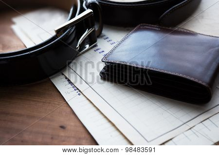 Documents, belt and a wallet on a wooden desk. hotel table or gentleman's desk. shallow depth of field.