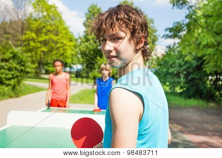 Boy with racket turned and playing table tennis