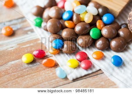 food, junk-food, culinary, baking and eating concept - close up of jelly beans and chocolate candies on table