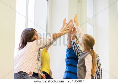 education, elementary school, learning, gesture and people concept - group of school kids making high five gesture at corridor