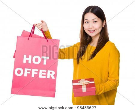 Woman hold shopping bag and gift box with showing hot offer
