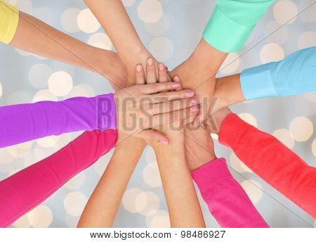 people, gesture, gay pride and homosexual concept - close up of women hands in rainbow clothes on top of each other over holidays lights background