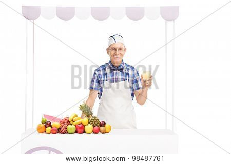 Senior soda jerk holding a glass of lemonade and standing behind a stall with a bunch of fruits on it isolated on white background