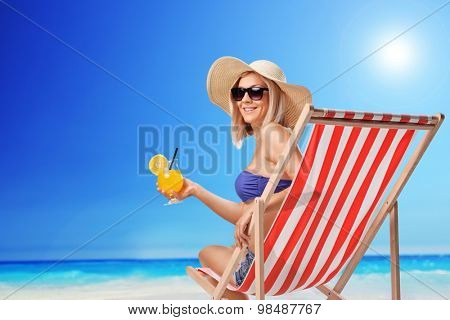 Young woman sitting on a sun lounger with an orange cocktail in her hand and looking at the camera at a sunny beach