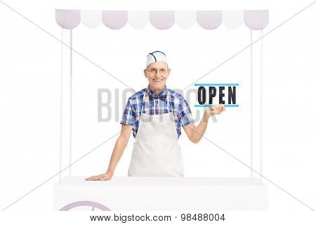 Studio shot of a senior vendor holding an open sign and posing behind a stand isolated on white background