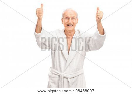 Studio shot of an overjoyed senior in a white bathrobe giving two thumbs up and looking at the camera isolated on white background