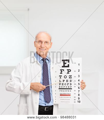 Mature optician holding an eye chart and pointing on it with a wooden stick in a hospital