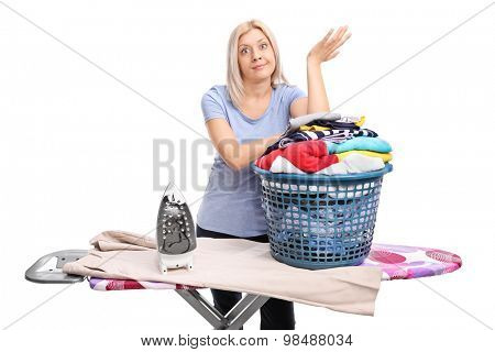 Annoyed young woman standing behind an ironing board and gesturing with her hand isolated on white background