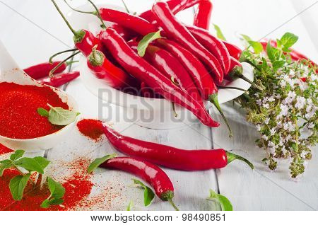 Red Chili Peppers With Fresh Herbs In  A White Bowl.