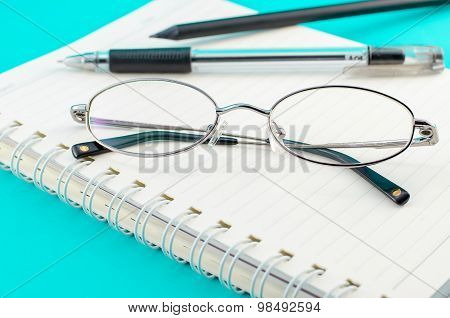 Old Glasses With Pen And Pencil On Open Notebook