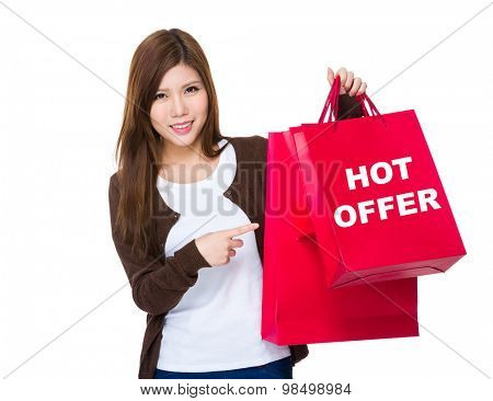 Young woman finger point to shopping bag hot offer