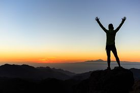 stock photo of motivation  - Woman successful hiking climbing silhouette in mountains motivation and inspiration in beautiful sunset and ocean - JPG