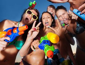 pic of pistols  - Group of young joyful young people playing and posing with water pistols on the beach  - JPG