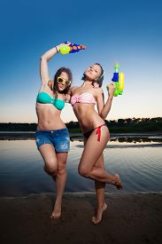 stock photo of pistols  - Two young girl posing with water pistols - JPG