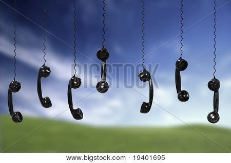Multi old-fashioned telephones over a green meadow