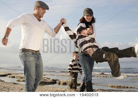 família feliz de quatro jogando na praia