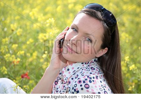 pretty young woman talking on mobile phone on a meadow