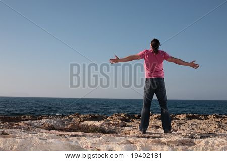 young man with arms wide open affirmating the sea