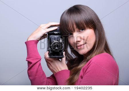 Young beautiful smiling woman holding a vintage photo camera