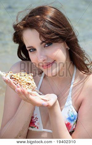 beautiful Teen Girl in Bademode hält eine Muschel am Strand sitzen