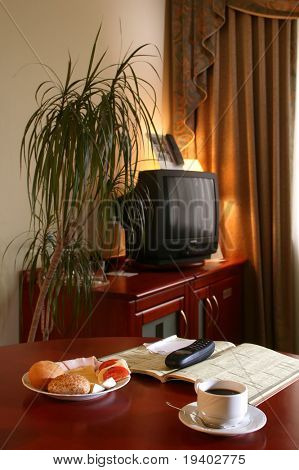 A comfortable hotel room with a light continental breakfast including coffee and business book on a table.