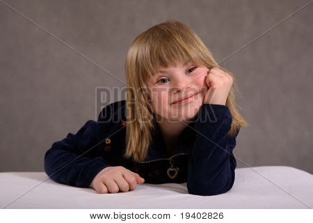 A portrait of a blond 9-year old girl with Downs Syndrome