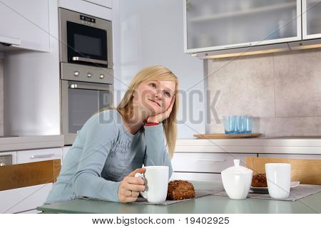 Joven mujer rubia tomando café en su cocina