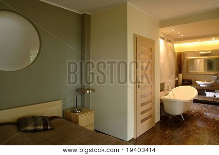 An interior photo of a nicely decorated master bedroom and bathroom in a luxury apartment.