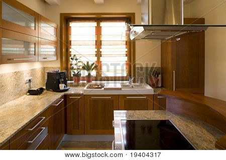 A view of a new, modern, well furnished home kitchen.