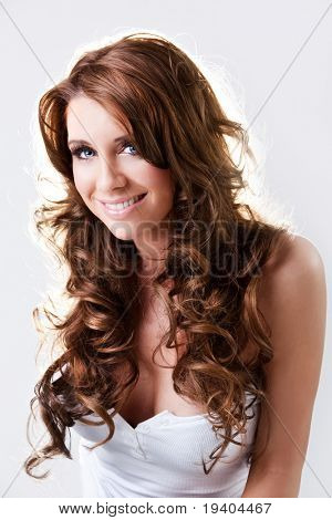 Beautiful blue eyed brunette with curly hair happily smiling