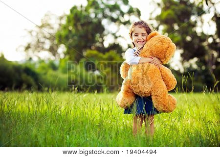 Little cute girl standing in the grass holding large teddy bear