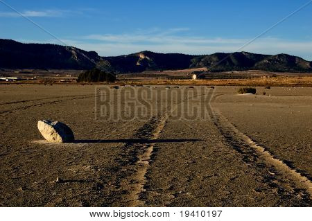 Dry salt lake - desert landscape, trace of tires detail - global warming, climate change - Laguna de Salinas (Spain)