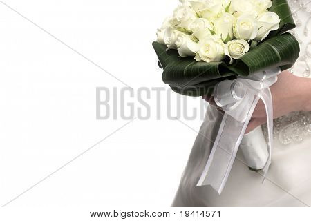 Wedding bouquet of white roses and green leaves in bride's hands