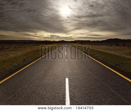 Alquitrán recto camino que conduce a la luz (imagen tonificada)