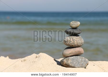 Five differently sized and colored pebbles, stacked over a sea