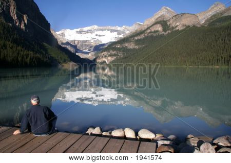 Lake Louise With Man Sitting On A Dock