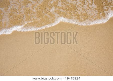 Wave of water on clear sandy beach