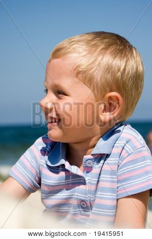 3 years old boy wearing casual clothes and smiling on a beach