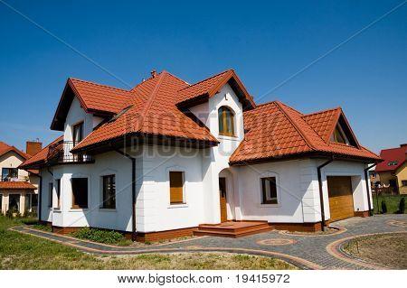 Kleine weiße Einfamilienhaus gegen blauen Himmel
